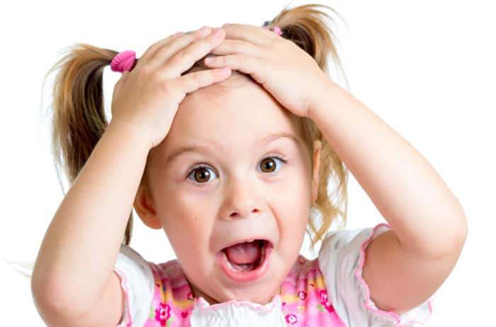 little girl with hands on her head, mouth open