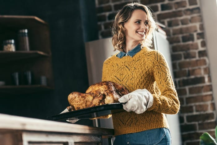 woman carrying cooked turkey