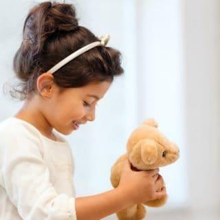 Girl child holding a teddy bear