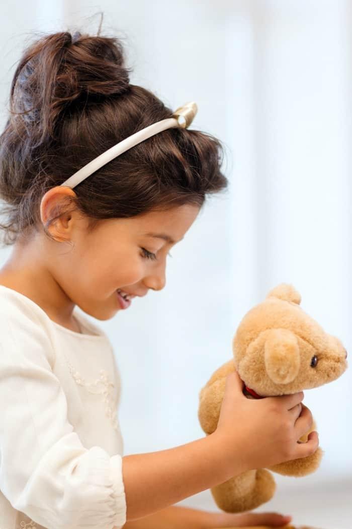 Girl child holding teddy bear