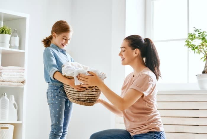 women and child holding a laundry basket