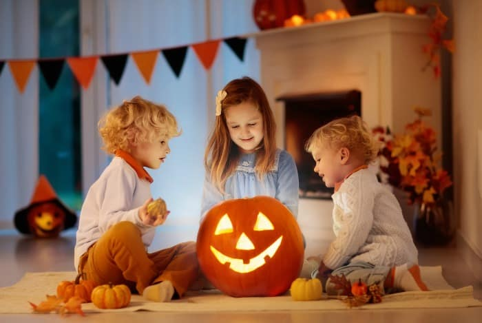 kids sitting around a jack o lantern