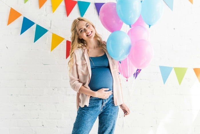 pregnant woman with balloons and streamers